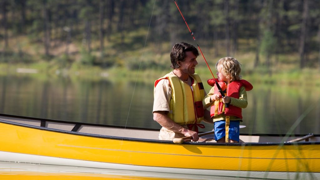 father and son fishing in canoe