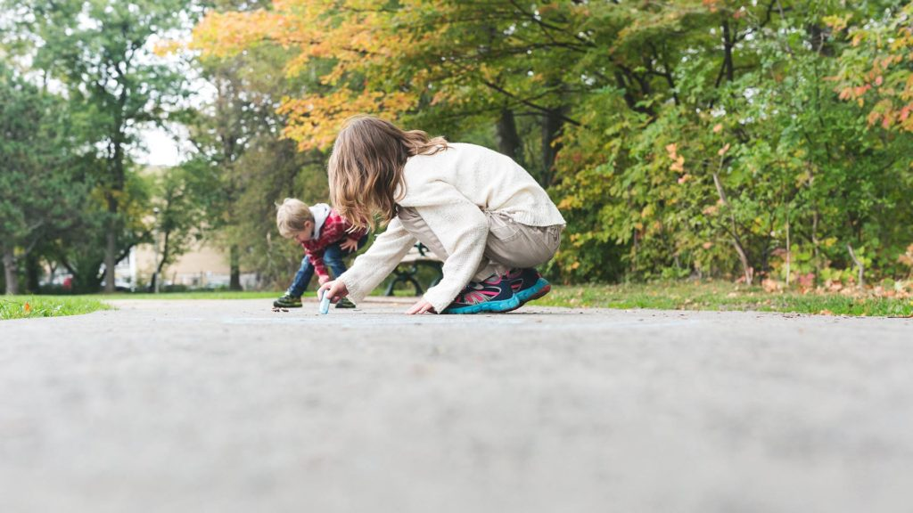two children drawing with chalk on a sidewalk