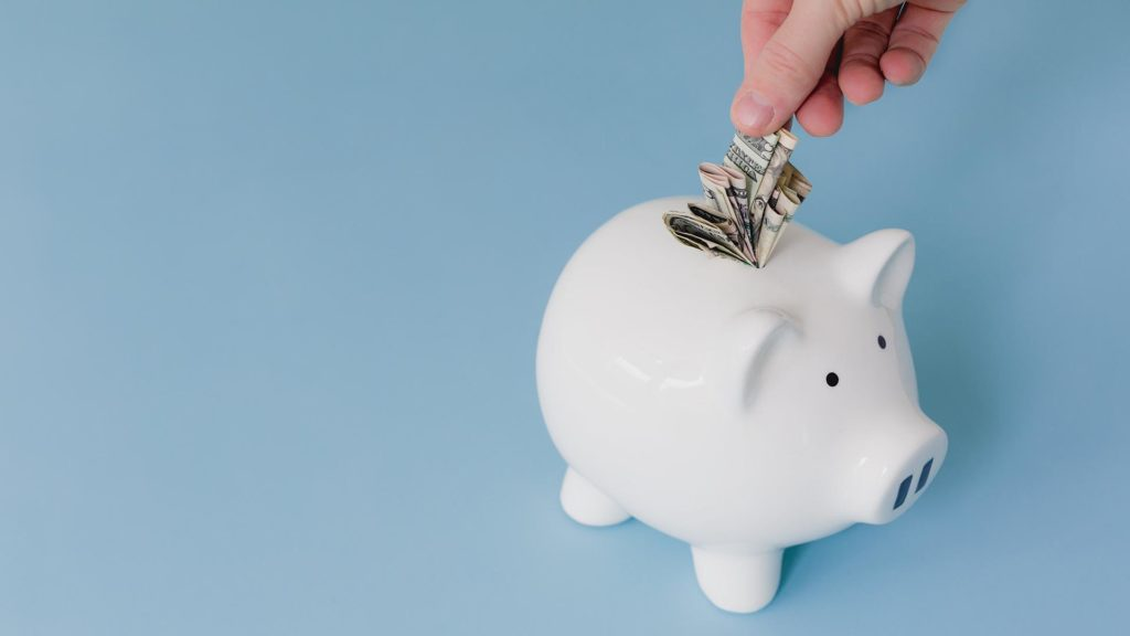 hand putting money into a full piggy bank